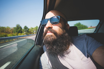 Bearded man looking out of car window on highway, Garda, Italy