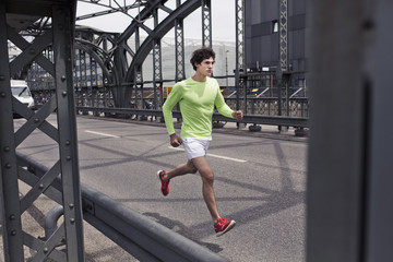 Young man running across urban bridge