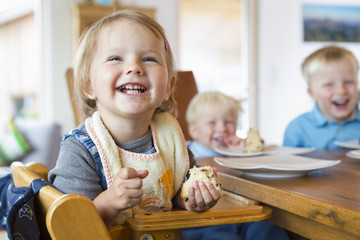 Three young children eating cake at tea table