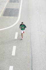 High angle view of young male runner running at parking lot