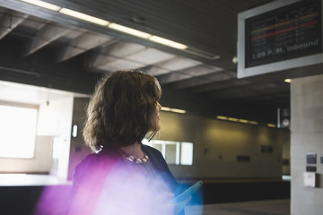 Mid adult woman at train station, holding smartphone Wall mural