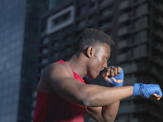 Portrait of boxer throwing punch, building in background