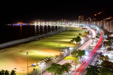 Aerial view of Capacabana Beach by night in Rio de Janeiro. The evening mist covers the shoreline, while cars leave long exposure light trails on Av. Atlantica