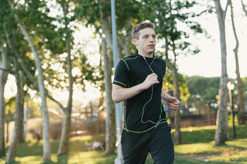 Young man running, outdoors, wearing earphones