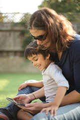 Side view of boy sitting on mother's lap using digital tablet looking down smiling