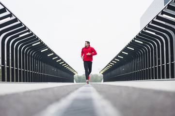 Surface level view of young male runner running over city footbridge