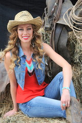 Cowgirl relaxing on haystacks inside a barn.