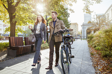 Casual businessman and woman pushing bike through park