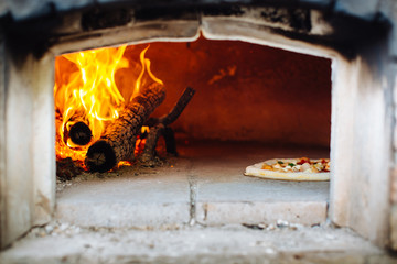 Pizza in traditional pizza wood oven