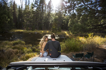 Rear view of romantic young couple sitting on jeep hood at riverside, Lake Tahoe, Nevada, USA