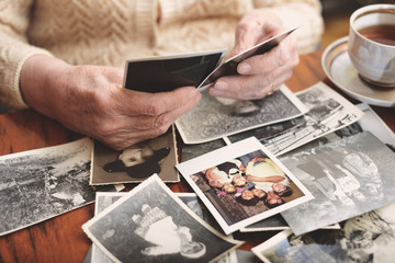 Senior woman sitting at table, looking through old photographs, mid section