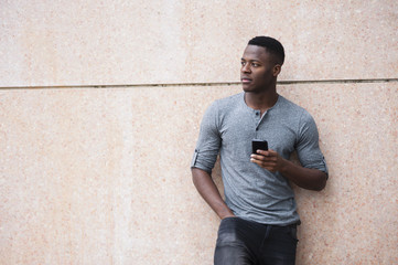 Portrait of young man, leaning against wall, holding smartphone