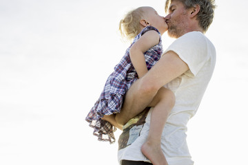 Side view of female toddler and father kissing