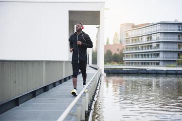Young man running beside river