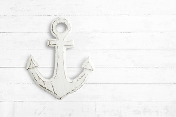 Old wooden white anchor on white rustic wood table, top view