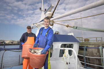 Fishermen with catch of fish on deck of trawler, portrait