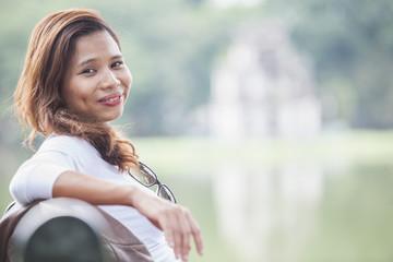Portrait of woman with long brunette hair sitting at Hoan Kiem Lake, Hanoi, Vietnam