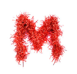 Tinsel Christmas decoration in form of M. On a white background