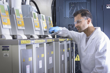 Scientist with lithium ion battery aging equipment in battery research facility
