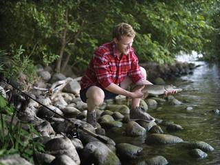 Fisherman crouching on riverbank holding fish, Denmark