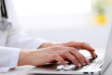 Close-up of female doctor typing laptop sitting at a table in the hospital