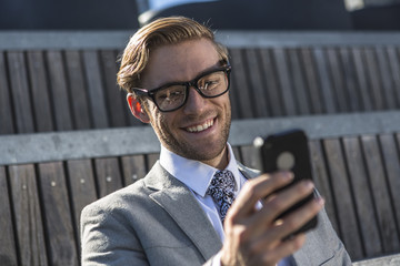 Young businessman reading smartphone text in city
