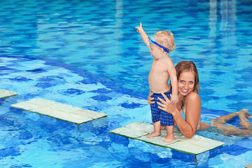 Little happy sports man in underwater goggles - active baby swim with fun, jump to mother hands in swimming pool. Family lifestyle and summer children water activity and swimming lesson with parents.