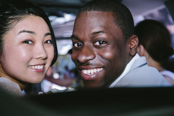 Portrait of couple looking over shoulder at camera smiling
