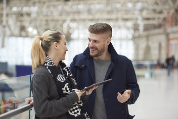 Young couple at train station, using digital tablet, smiling