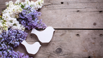 Flowers and decorative birds on wooden table.