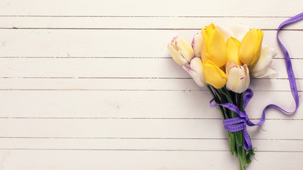 Bright yellow and white spring tulips on white wooden background