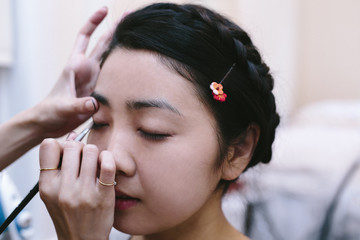 Hands of make up artist applying make up on young woman with eyes closed