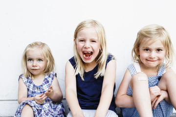 Portrait of three young sisters sitting in front of white wall
