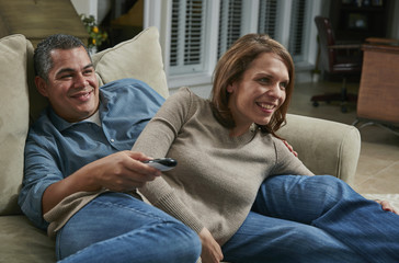 Couple snuggling on sofa, looking away using remote control smiling