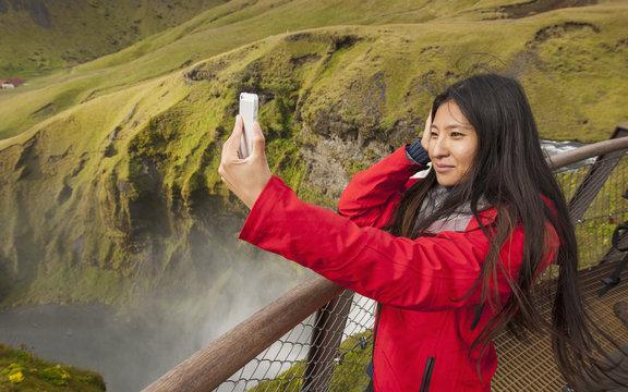 Mid adult woman taking smartphone selfie at Skogafoss waterfall, Iceland