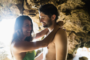 Romantic young couple in cave on Newport Beach, California, USA