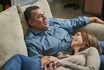 Couple snuggling on sofa, head in lap face to face smiling