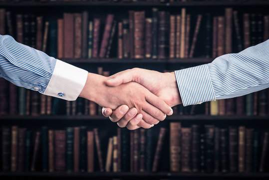 握手をしている二人 本棚の背景