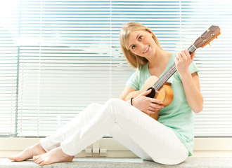 beautiful blond woman plays guitar near venetian blind window