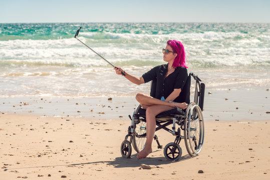 Disabled woman in the wheelchair taking selfie photos