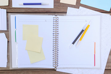Notebook with colorful pens and sticky notes with space for text