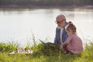 Grandfather reading fairy tale to granddaughter outdoors