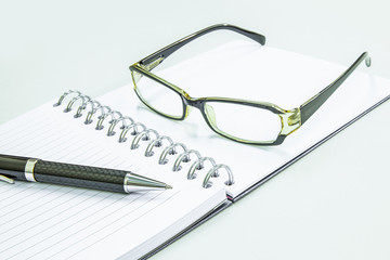 Pen notepad and glasses on white background