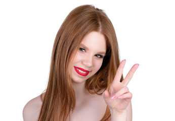 The girl smiles and shows the two fingers gesture