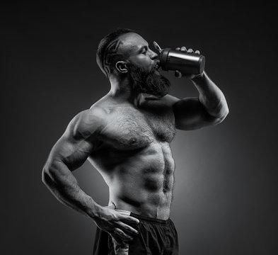 Bearded Man bodybuilder posing on gray background