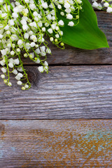 white flowers lilies of the valley scattered on the old wooden background. with space for text
