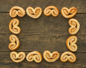 Frame from puff sweet pretzels with cinnamon  on the wooden background