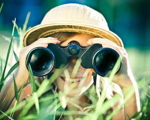 beautiful young explorer girl with hat and binocular at park