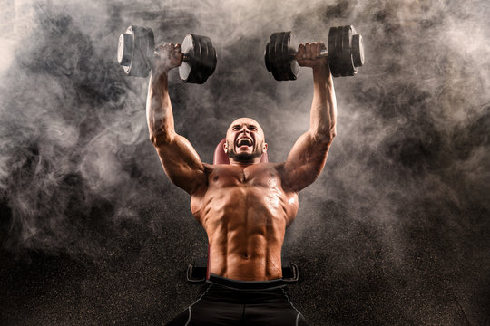 Topless muscular man doing dumbbell exercise on bench press