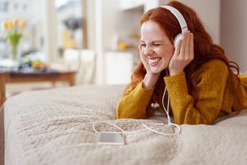 lachende junge frau hört musik zu hause und lacht